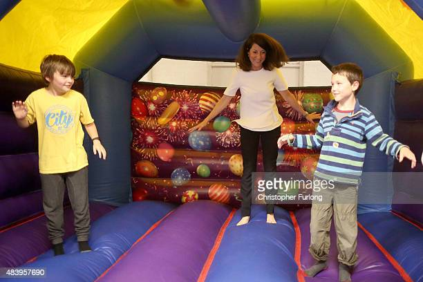 Labour party leadership candidate Liz Kendall joins children on a bouncy castle during a visit to the Kidszone children's centre in Withington on...