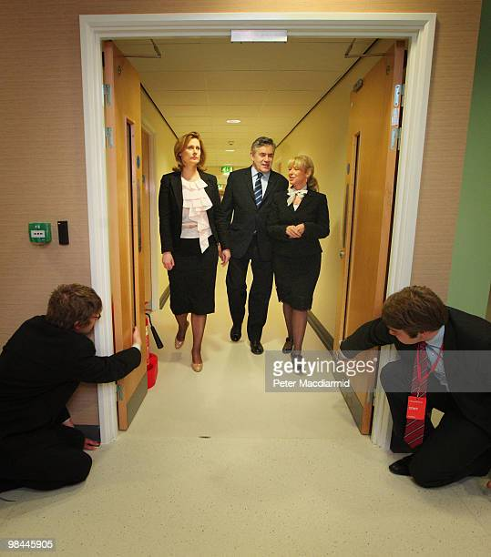 Labour party officials hold the doors open as Prime Minister Gordon Brown and his wife Sarah walk with Sam Prince from the National Health Service...
