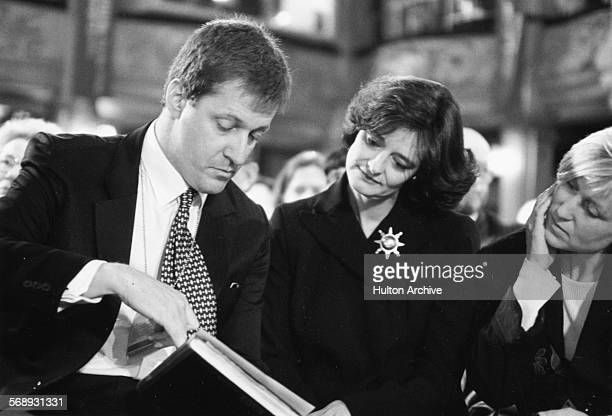 Labour Party political aide Alastair Campbell and barrister Cherie Blair wife of Prime Minister Tony Blair reading from a hymn book in church during...