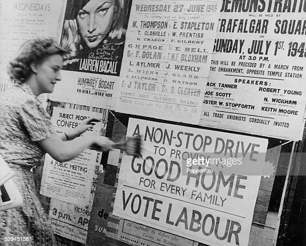 A Labour Party supporter puts up a poster reading 'A Nonstop Drive to Provide a Good Home for Every Family Vote Labour' in the runup to the General...