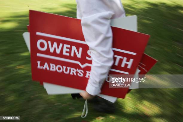A Labour supporter carries Owen Smith's placards way after an event for young members in London Fields Hackney in London on August 7 2016 Labour has...