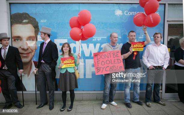 Labour supporters dressed as 'Tory Toffs' and carrying ballons stand outside the office of conservative parlimentary candidate Edward Timpson before...