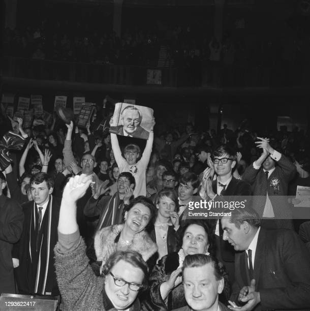 Labour supporters hold up a photograph of Prime Minister Harold Wilson in Kemptown, Brighton, UK, after Labour's win in the 1966 General Election,...