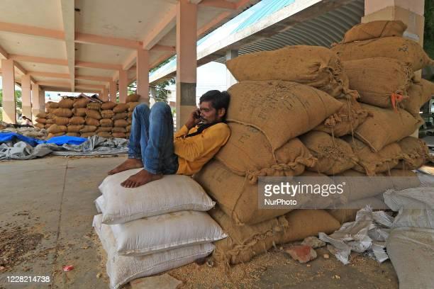 Labour talk on phone at Kukar Kheda Grain Market after 4 days strike announced by Rajasthan Khadya Padarth Vypar Sangh against the various central...