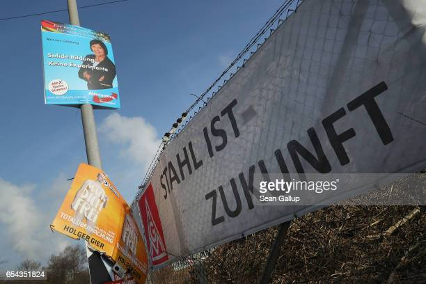 A labour union banner reads 'Steel is the future' outside the Dillinger Huette steelworks under election campaign posters on March 15 2017 in...