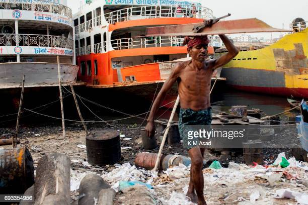 SADARGHAT DHAKA BANGLADESH A labourer carrying metal beside the Burigonga River on the day before of World Environment Day A large swathe of the...