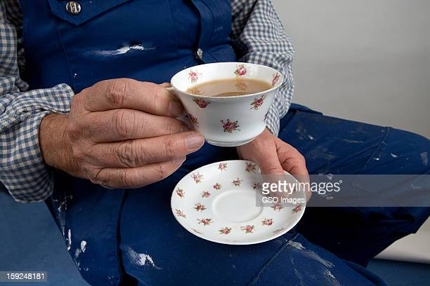 A labourer holds a delicate cup of tea and saucer
