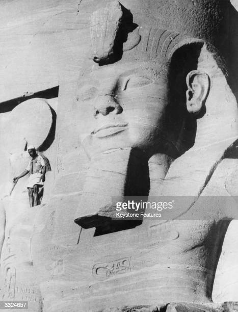 A labourer involved in the project to move Egyptian temples away from the waters of the Aswan Dam stands next to the huge statue of Ramses II which...