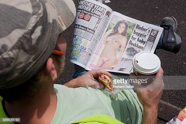 A labourer reads a copy of Britain's tabloid Sun Newspaper The worker holds a coffee and wears a working mans' cap with a pencil in his right ear as...