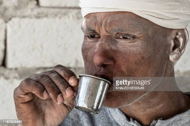 """Labourer sips on a cup of tea at the """"White Mountain"""" limestone extraction quarry site near Egypt's southern city of Minya, some 265 kilometres south..."""