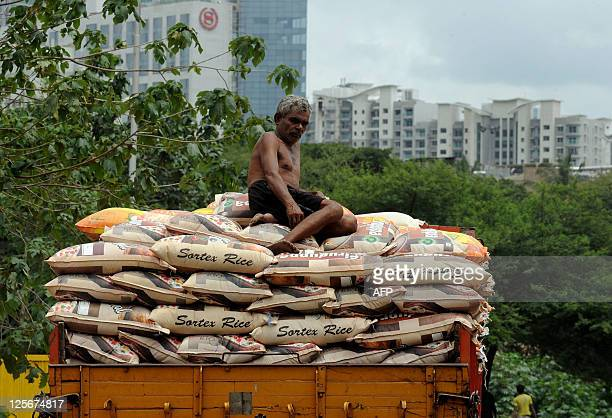 Labourer sits on sacks of rice loaded on a truck at the Agricultural Product Marketing Committee Yard in Bangalore on September 20, 2011. India's...