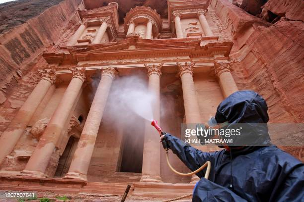 TOPSHOT A labourer sprays disinfectant in Jordan's archaeological city of Petra south of the capital Amman on March 17 to prevent the spread of...