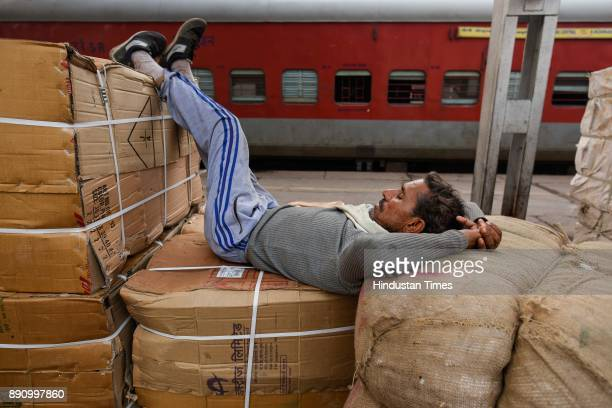 A labourer takes a nap on a cold day at Nizamudin railway station on December 12 2017 in New Delhi India