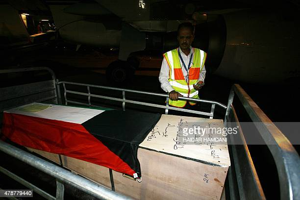 A labourer unloads one of the coffins of the eight victims of the suicide bombing on the AlImam AlSadeq mosque bombing in Kuwait ahead of their...