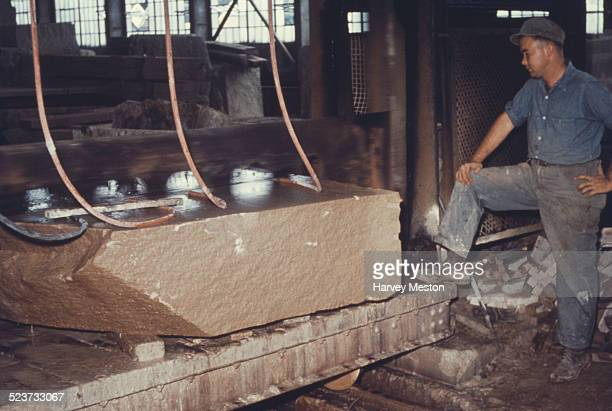 A labourer using an industrial saw to cut a block of wet limestone in Indiana circa 1960
