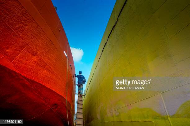 TOPSHOT A labourer walks on a ladder to climb on a ferry at a dockyard beside the Buriganga river in Dhaka on October 18 2019