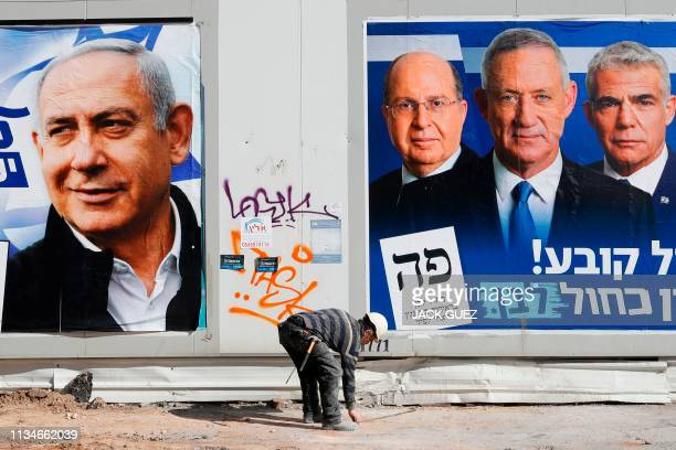 A labourer walks past electoral campaign posters bearing the portraits of Israel's Prime Minister Benjamin Netanyahu leader of the Likud party and...