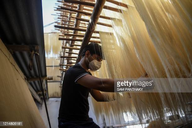 Labourer wearing a facemask dries vermicelli at a workshop in Ahmedabad on May 23, 2020.
