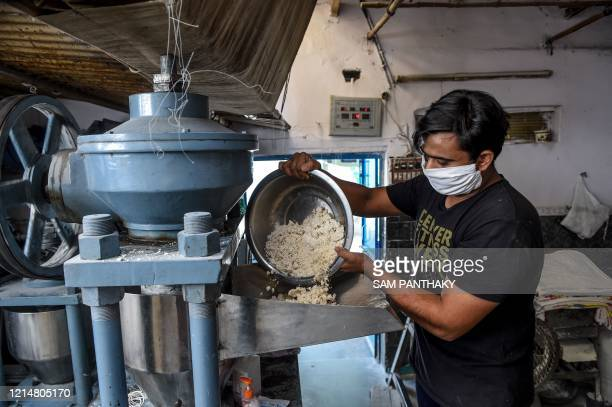 Labourer wearing a facemask pours ingredients to make vermicelli at a workshop in Ahmedabad on May 23, 2020.