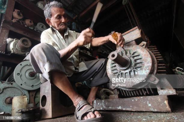 A labourer works inside a motor pump workshop in Mumbai India on 03 September 2019