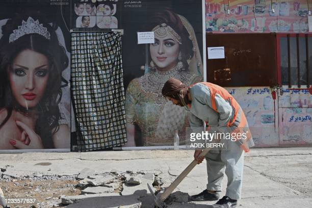 Labourer works on a pavement project outside a beauty parlor in Kabul on June 21, 2021.