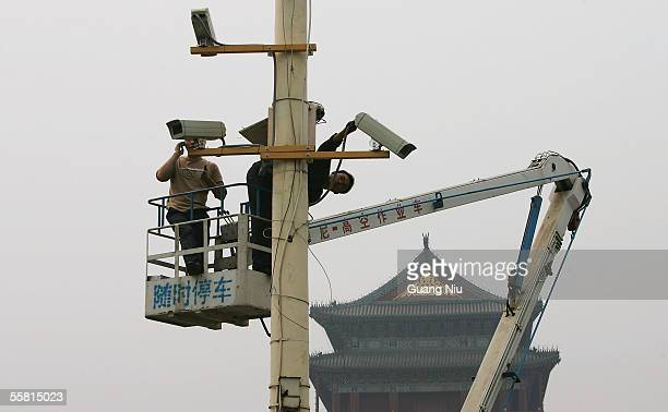 Labourers adjust newly installed surveillance cameras at Tiananmen Square ahead of National Day on September 28 2005 in Beijing China The capital...