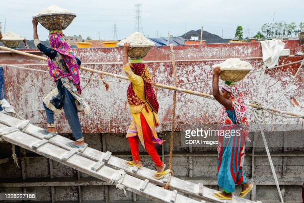 Labourers are seen unloading sand from a cargo ship in Gabtoli. They are earning around $1 every 30 baskets of sand unloaded from the ship.