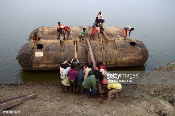 Labourers build a floating pontoon bridge on the Ganges River during preparations ahead of the annual Hindu religious fair of 'Magh Mela' in...