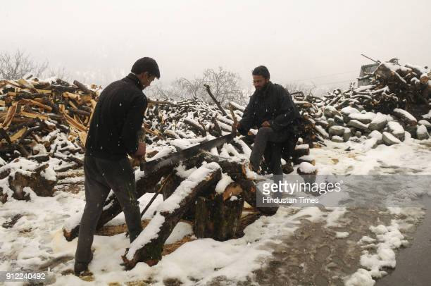 Labourers busy in cutting logs of wood after fresh snowfall on January 30 2018 in Tangmarg some 40 kilometers north of Srinagar India The sevenweek...