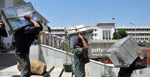 Labourers carry boxes containing official records of Jammu and Kashmir states' Civil Secretariat for loading into the trucks on April 30 2016 in...