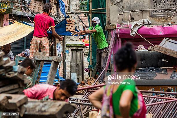 Labourers clear bricks from a destroyed building in Kathmandu on July 25, 2015. Today marks the 3 month anniversary of the Nepal earthquakes which at...