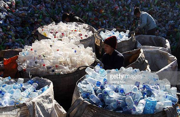 Labourers collect assorted plastic products from a garbage pile at a recycling center on the outskirts of the city on December 17 2008 in Beijing...