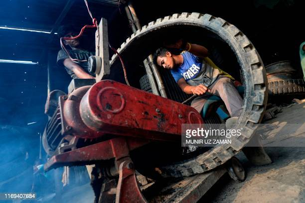Labourers cut a used tyre with a machine in Dhaka on September 19 2019