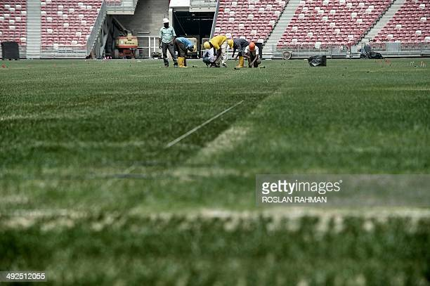 Labourers fixing the pitch of the new national stadium at sports hub complex in Singapore on May 21 2014 The 55000 allseater National Stadium is the...