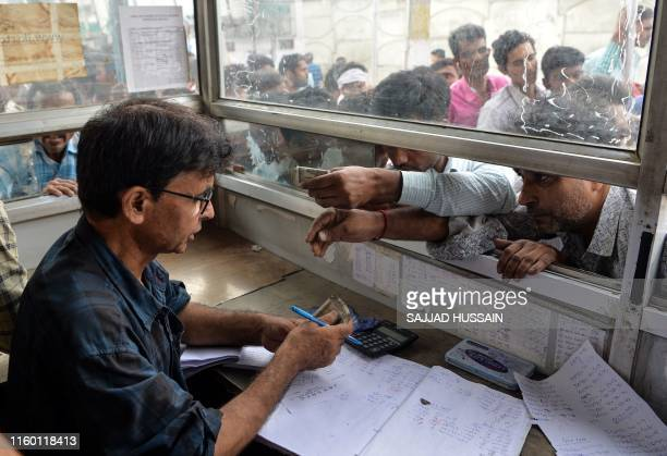 TOPSHOT Labourers from across India working in Kashmir buy bus tickets at a counter of Jammu and Kashmir Tourist Reception Centre to leave the city...