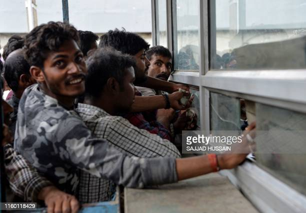 Labourers from across India working in Kashmir buy bus tickets at a counter of Jammu and Kashmir Tourist Reception Centre to leave the city due to...