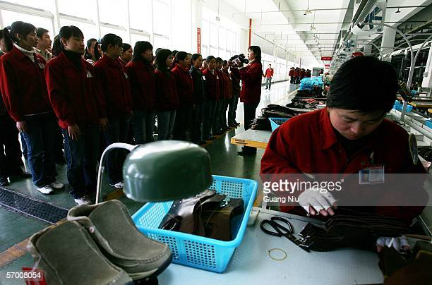 Labourers line up to listen a shoe production instruction at a leather shoe factory on March 3 2006 in Wenzhou of Zhejiang Province China Wenzhou is...