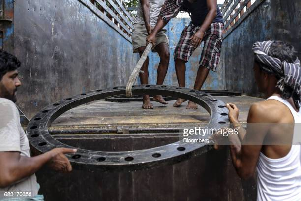 Labourers load a metal ring onto the back of a truck near Manish Market in Mumbai India on Saturday May 13 2017 A Goods and Services Tax for India...