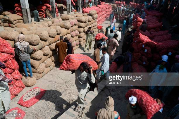 Labourers loads potato sacks onto a truck in a market on the eve of the International Labour Day in Lahore on April 30 2020