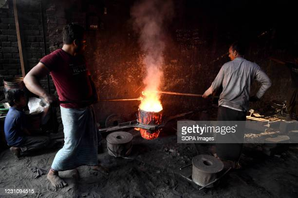Labourers prepare to pour molten iron in a mould to make a propeller at a workshop on the banks of the Buriganga river in Dhaka. The shipbuilding...