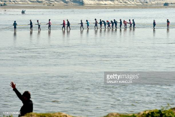 Labourers pull a pontoon buoy with ropes in the banks of river Ganges to build a bridge during preparations for the annual Hindu religious fair of...