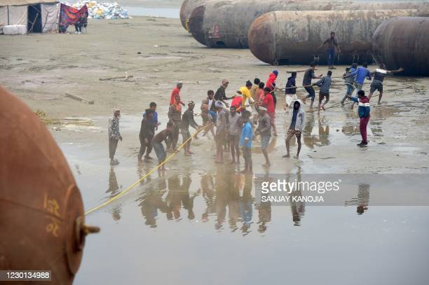 Labourers pull a pontoon buoy with ropes in the banks of the Ganges River to build a bridge ahead of the Magh Mela festival in Allahabad on December...