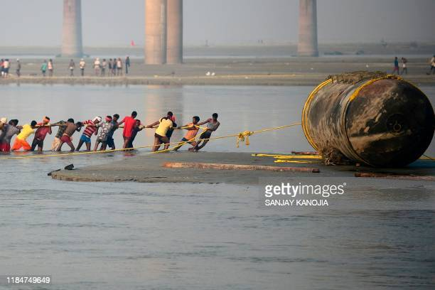 Labourers pull a pontoon buoy with ropes in the Ganges river as they build a floating pontoon bridge for the upcoming Hindu festival of Magh Mela in...