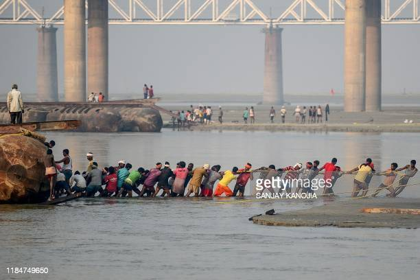 TOPSHOT Labourers pull a pontoon buoy with ropes in the Ganges river as they build a floating pontoon bridge for the upcoming Hindu festival of Magh...