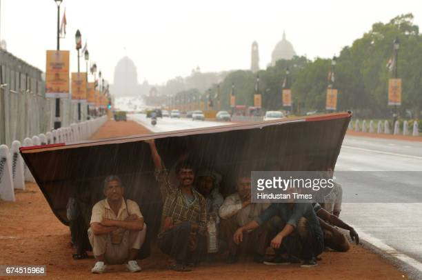 Labourers take shelter under a giant hoarding during a sudden downpour near India Gate on April 28 2017 in New Delhi India