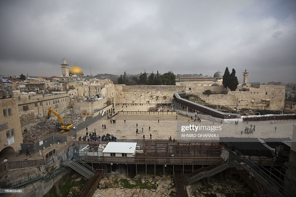 Labourers use a bulldozer to raze a Israeli building in the Western Wall plaza of Jerusalem's Old City with the Dome of the Rock mosque and Al Aqsa mosque compound in the background, on February 6, 2013. According to Al-Aqsa Foundation which campaigns for the defence of Islamic holy sites, the Israeli bulldozers are demolishing the frontages and arches of an historic Islamic building few dozen meters away from the Al-Aqsa mosque compound. The Al-Aqsa foundation said in a statement the demolition paves the way for an Israeli project to build a complex including a synagogue, a reception hall and a police station.