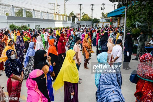 Labourers wait in lines to collect their salary in a garment factory during a government-imposed lockdown as a preventative measure against the...