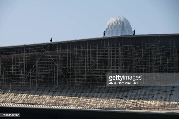 Labourers walk above bamboo scaffolding on the roof of the Convention Centre in Hong Kong's Wanchai district while the 88storey tall IFC building is...
