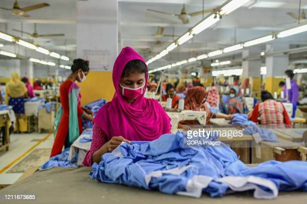 Labourers wearing face masks as a preventive measure work at a garment factory during the lockdown New Generation Fashion Limited workers resume on...