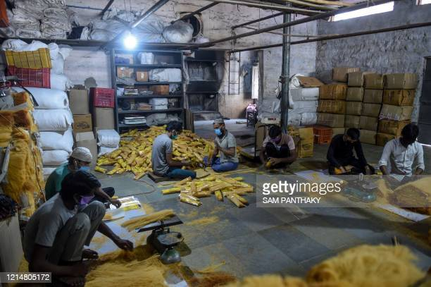 Labourers wearing facemasks pack vermicelli at a workshop in Ahmedabad on May 23, 2020.